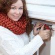 Stock Photo: Womcontroling temperature of heating radiator