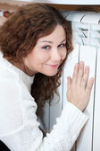 Central heating radiator and attractive woman — Stock Photo