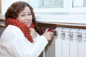 Woman feels cold when turning thermostat — Stock Photo