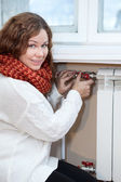 Woman in warm clothes controling the temperature in domestic room — Stok fotoğraf