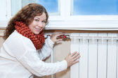 Woman in front of heating radiator in domestic room — Stock Photo