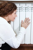 Central heating radiator and woman leaning his hand — Stock Photo