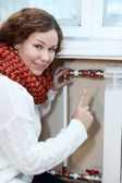 Smiling woman gesturing when turning thermostat on central heating — Stock Photo