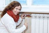 Woman controling thermostat on central heating radiator — Stok fotoğraf