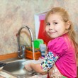 Girl in the kitchen ashing dishes, copyspace — Stock Photo