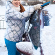 Happy woman removing snow from car bonnet in winter — ストック写真