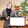 Office employee stands next to blank white screen monitor — Stock Photo #40508609