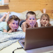Three children looking at laptop — Stock Photo #40508637