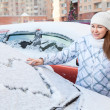Woman drawing heart shape on snowy car — Stock Photo