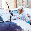 Woman with snow brush near snowy car — Stock Photo #40509029