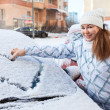 Woman standing near snowy car — Stock Photo #40509037