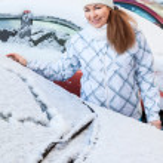 Woman drawing heart shape on snowy car — Stock Photo
