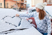 Woman drawing heart on car — Stockfoto