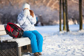 Young woman with backpack in winter park — Stock Photo