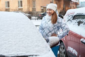Woman standing near snow covered car — Stock Photo