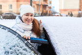 Woman with snow brush near snowy car — Stock Photo