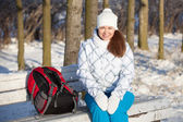 Woman with backpack resting on a bench in winter park — Stock Photo