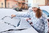 Woman standing near snowy car — Stok fotoğraf