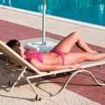 A beautiful young girl in a bikini sunbathing on a lounger near pool — Stock Photo #4251404