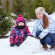 Family making snowman — Stock Photo