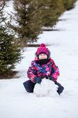 Girl making  snowman — Foto Stock