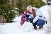Family sitting in snow — Stock Photo