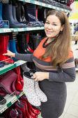 Merchandiser showing waterboots — Stock Photo