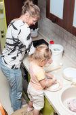 Mère aider l'enfant à cuire — Photo