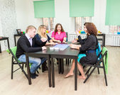 Group of young people sitting at table and playing games — Stock Photo