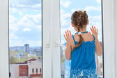 Child looking through window — Stock Photo