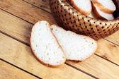 Two slices of bread near wicker breadbasket — Stock Photo
