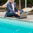 Young Businessman with Computer next to Swimming Pool — Stock Photo #12572774