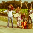 Hippie Group Hitchhiking on Countryside Road — Stock Photo #12643703
