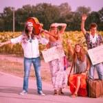 hippie grupp lifta på landsbygden väg — Stockfoto