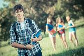 Estudiante joven con amigos en el parque — Foto de Stock