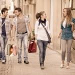 glada tjejer med uttråkad pojkar på shopping — Stockfoto