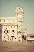 Groep vrienden springen met scheve toren van pisa op achtergrond — Stockfoto