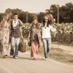 Groupe de hippie marchant sur une route de campagne — Photo