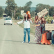 Hippie Group Hitchhiking on Countryside Road — Stock Photo #12841939