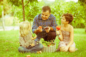 Adult Farmer with Children and Harvested Vegetables — Stock Photo