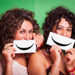 Two Young Women with Smiley Emoticon on Green Background — Stock Photo #13172342