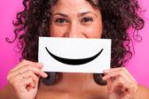 Mujer joven con emoticon sonriente sobre fondo fucsia — Foto de Stock