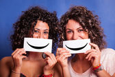 Two Young Women with Smiley Emoticon on Blue Background — Stock Photo