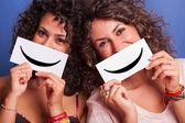 Duas mulheres jovens com emoticon smiley em fundo azul — Foto Stock