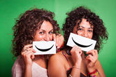 Two Young Women with Smiley Emoticon on Green Background — Stock Photo