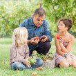 Adult Farmer with Children and Harvested Vegetables - Stock Photo