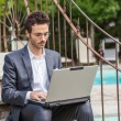 Young Businessman with Computer next to Swimming Pool — Stock Photo #13205418