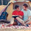 Stock Photo: Young Couple Camping and Reading a Book