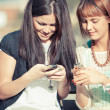 Stock Photo: Two Young Women with Mobile Phone
