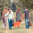 Hippie Group Walking on a Countryside Road — Stock Photo #13655899